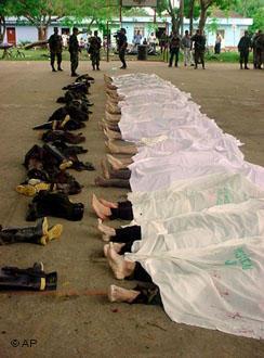 Soldados observan los cuerpos de rebeldes muertos.